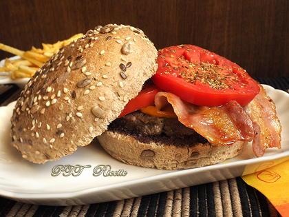 Panino con hamburger, paté di olive e pomodoro